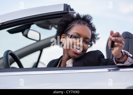 Young beautiful black woman driver holding car keys driving her new car - Stock Photo