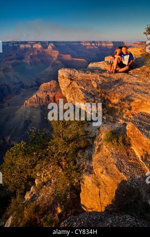 Kids on rock at Sunset at Yavapai Point, South Rim, Grand Canyon National Park, Arizona - Stock Photo