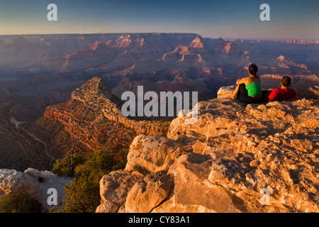 Tourist couple watching the sunset from Grandview Point, South Rim, Grand Canyon National Park, Arizona - Stock Photo