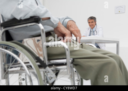 Doctor working in office, patient in wheelchair in foreground - Stock Photo