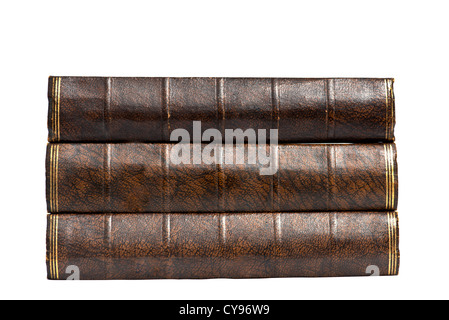 The spines of three brown hardback vintage retro antique books in a neat stack pile isolated isolation on white - Stock Photo