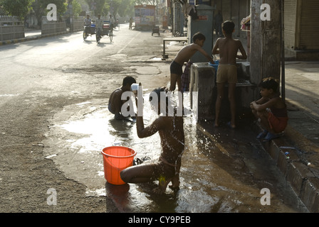A teenager has an early morning wash on the street in Old Delhi, India - Stock Photo
