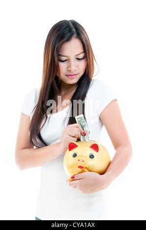 Pretty young woman putting money into piggy bank, portrait - Stock Photo