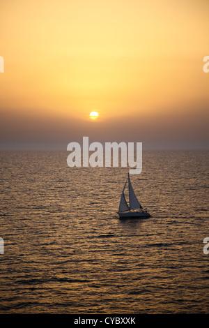 Yacht sailing at sunset near Bari. Italy. - Stock Photo