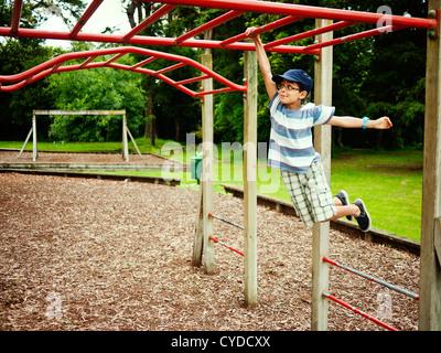 Children swing on monkey bars in adventure playground, New Zealand. - Stock Photo