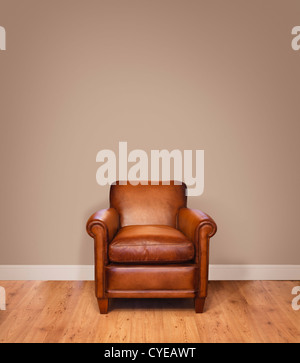 Leather armchair on a wooden floor against a plain background wall with lots of copyspace. The wall has a clipping - Stock Photo