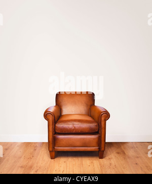 Leather armchair on a wooden floor against a white background with lots of space for copy.  The wall has a clipping - Stock Photo