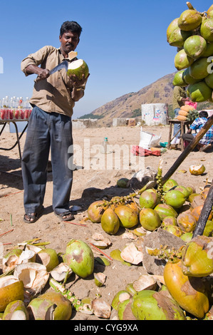 Vertical portrait of an Indian man preparing coconuts to drink with a machete at a roadside stall in Kerala. - Stock Photo