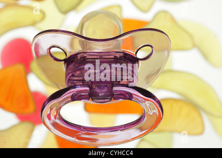 pacifier over sweets............ - Stock Photo