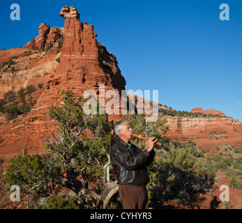 Arizona man plays Native American flute by Kachina Woman formation in Sedona, reached by hiking the Vista Trail - Stock Photo