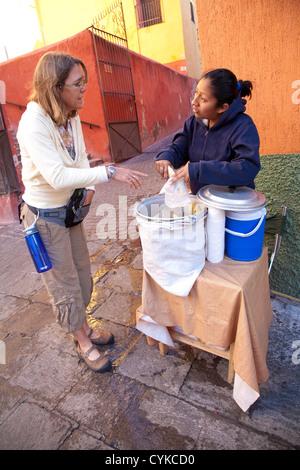 North America, Mexico, Guanajuato State, Guanajuato, woman buying hot tamales from street vendor. UNESCO World Heritage - Stock Photo