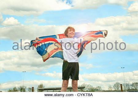 Boy wearing British flag outdoors - Stock Photo