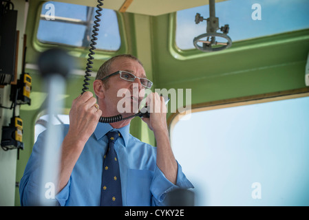 Tugboat captain talking on walkie talkie - Stock Photo
