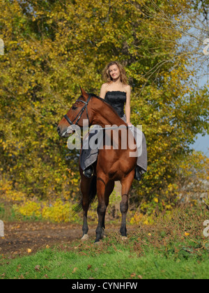 Cowgirl in vintage dress sitting on a horse - Stock Photo