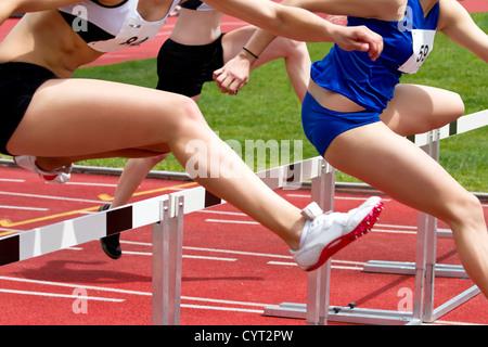 Female sprinter leaping over hurdles - Stock Photo