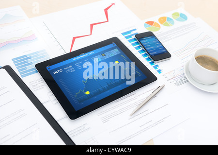 Modern business workplace with stock market data, mobile banking , some charts and graphs on a desk. - Stock Photo