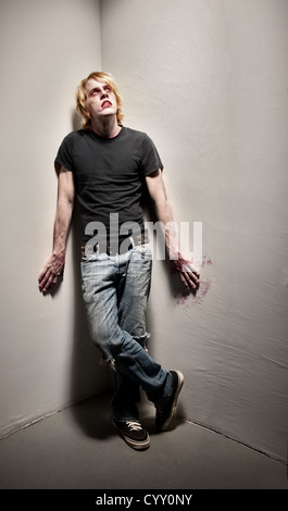 Young male zombie with bloody hands in corner - Stock Photo