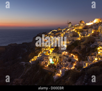 View of the Famous Oia sunset, with traditional houses and windmill along the cliff (Santorini, greece) - Stock Photo