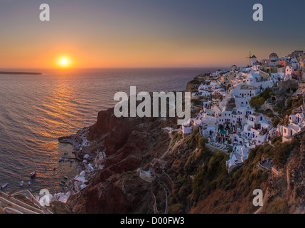 Traditional houses, harbour and windmill in Oìa at sunset. - Stock Photo
