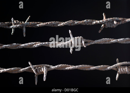 three rusty barbed wire on black background - Stock Photo
