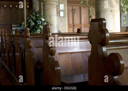 A row of pews in a traditional English church. - Stock Photo