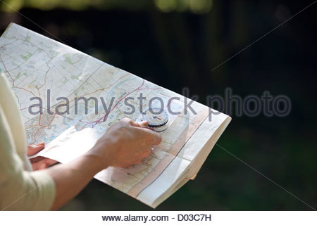 A woman holding a map and compass, close up - Stock Photo