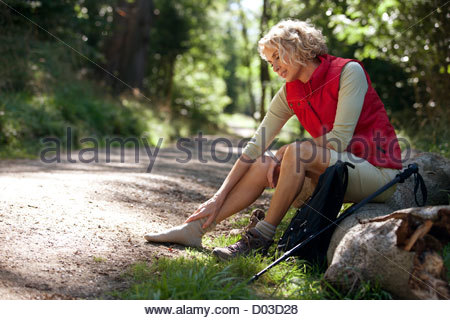 A mature woman resting beside a country path, massaging her sore feet - Stock Photo