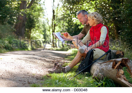 A mature couple resting beside a country path, looking at a map - Stock Photo