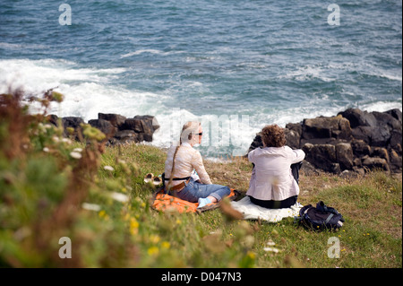 two  female holiday makers enjoying a rest on the south west coast path, england uk - Stock Photo