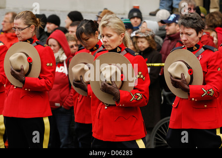Female R.C.M.P. in full red serge hats lowered attending a remembrance ceremony  in Vancouver. - Stock Photo