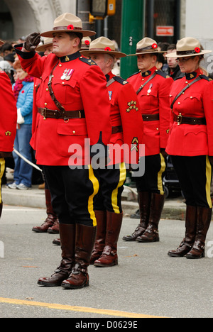 Saluting RCMP in full red serge at attention attending a remembrance ceremony  in Vancouver. - Stock Photo