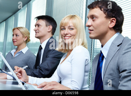 Blond businesswoman looking at camera at conference among her colleagues - Stock Photo