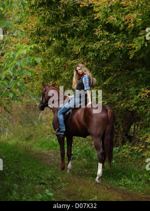 Happy cowgirl on brown horse - Stock Photo
