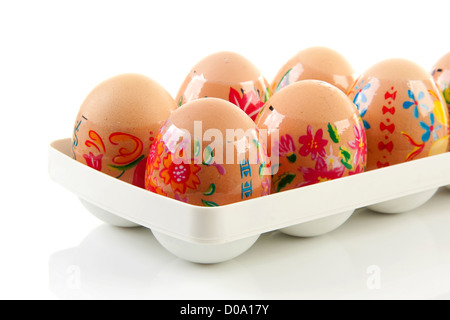 Decorated chicken eggs in holder made by children over white background - Stock Photo