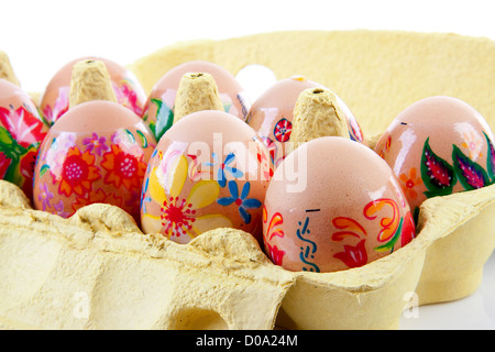 decorated chickens eggs made by children in carton over white background - Stock Photo