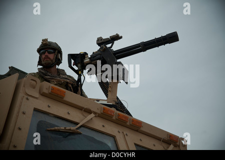 A coalition force member maintains security during a movement to visit Afghan National Security Force partners in - Stock Photo
