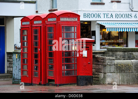 Traditional English red telephone boxes and postoffice pillar box on pavement in city street in England, UK - Stock Photo