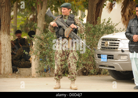 An Afghan National Army (ANA) soldier maintains a watchful eye during a visit from a high-ranking ANA officer at - Stock Photo