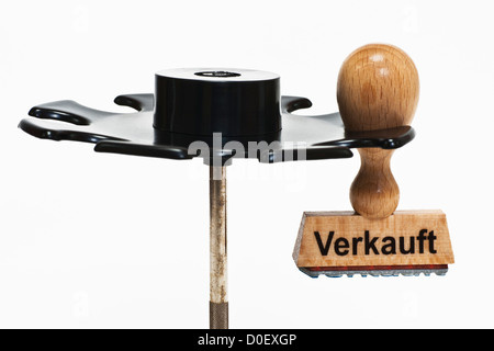 Stamp with German inscription Verkauft (sold) hangs in a stamp rack, background white - Stock Photo