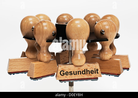 Many stamps hanging in a stamp rack, one with the German inscription Gesundheit (Health), background white. - Stock Photo