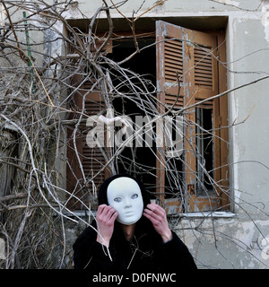 Grotesque white mask figure and haunted house window with tangled overgrown plants and creepy dummy doll hand. - Stock Photo