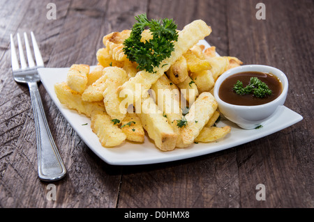Fresh fried French Fries on wood - Stock Photo