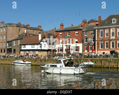 People relaxing along Kings Staith in spring. - Stock Photo