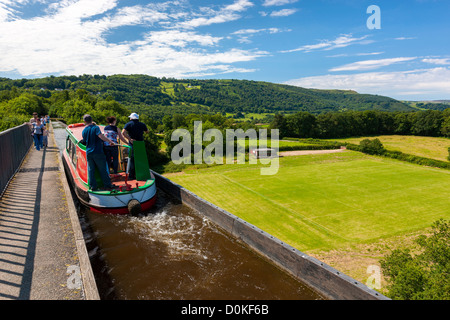 A barge travelling along the Pontcysyllte aquaduct which is a navigable aqueduct that carries the Llangollen Canal - Stock Photo