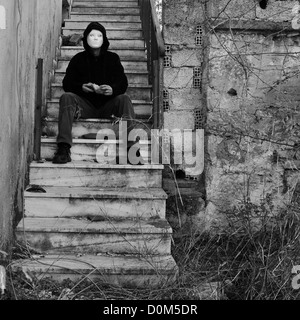 Masked figure with doll hand sitting on abandoned house staircase. Black and white. - Stock Photo