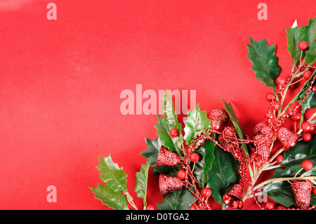 Twig of holly berry with red bells on red silk. Christmas decoration - Stock Photo