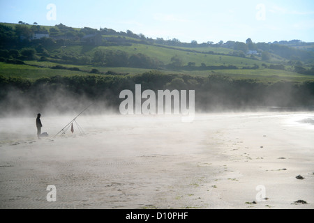 Sea mist and angler Poppit Sands St Dogmaeils Pembrokeshire Wales UK c - Stock Photo