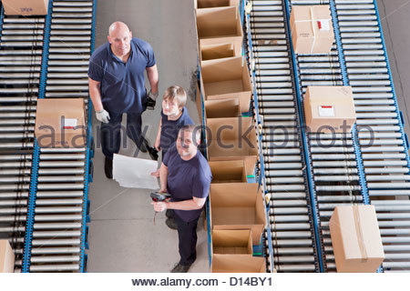 Portrait of workers packing boxes on conveyor belts in distribution warehouse - Stock Photo