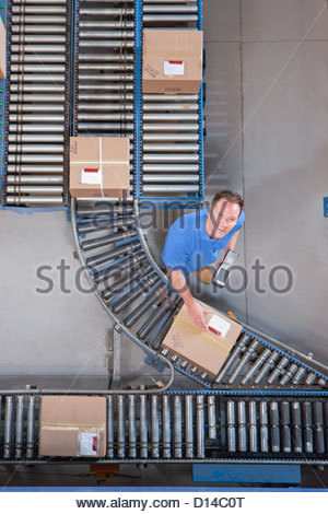 Portrait of smiling worker with bar code reader scanning box on conveyor belt in distribution warehouse - Stock Photo