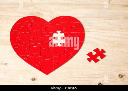 Heart shaped jigsaw puzzle with missing piece - Stock Photo
